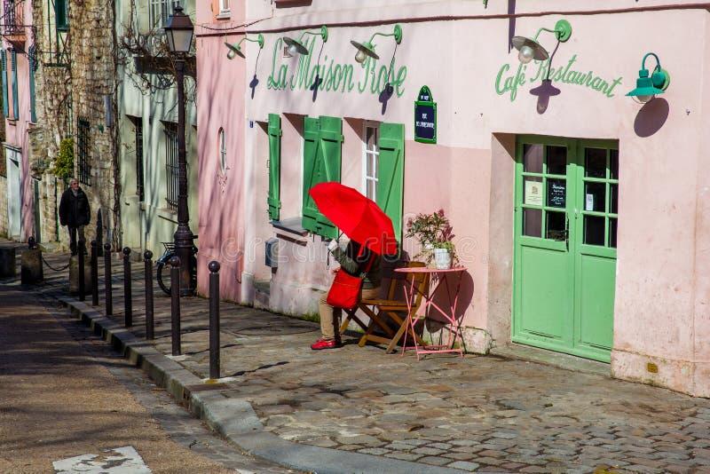 Dam med ett rött paraply på den rosa husrestaurangen i den berömda Montmartre royaltyfri fotografi