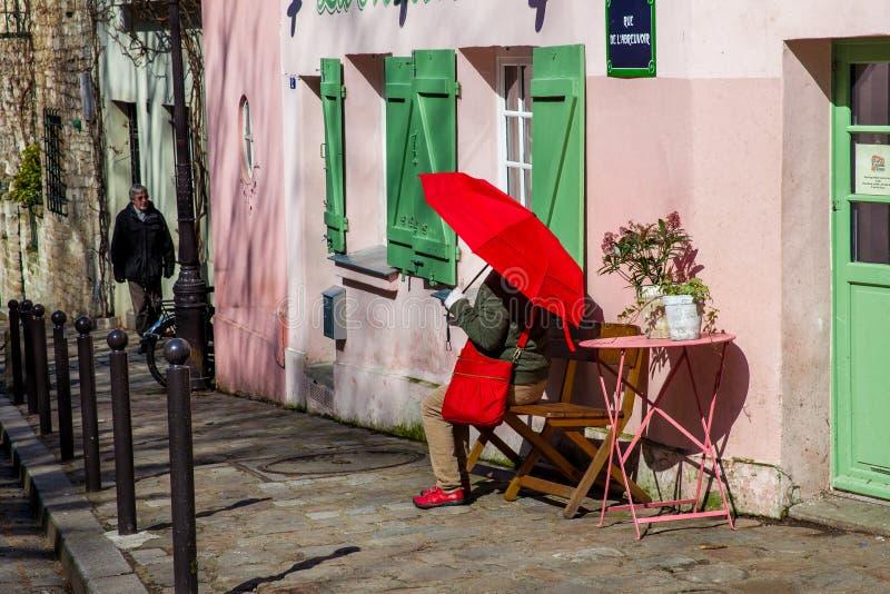 Dam med ett rött paraply på den rosa husrestaurangen i den berömda Montmartre royaltyfria bilder