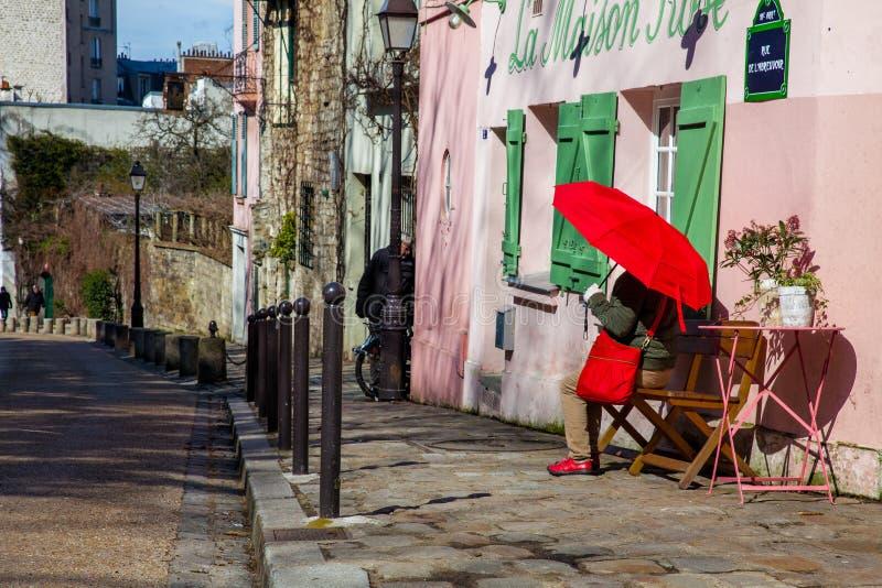 Dam med ett rött paraply på den rosa husrestaurangen i den berömda Montmartre royaltyfri foto
