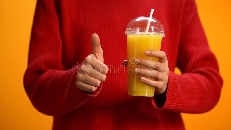 Dam med orange fruktsaft, hand som visar upp tummar, sund citrus coctail, energi arkivbilder