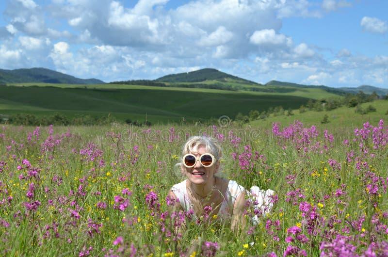 Dam med solglasögon, i att le för äng royaltyfri foto