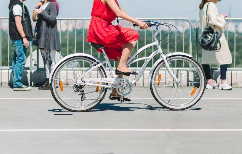 Dam på en cykel Flickan i den röda klänningen som rider en cykel runt om staden royaltyfria bilder