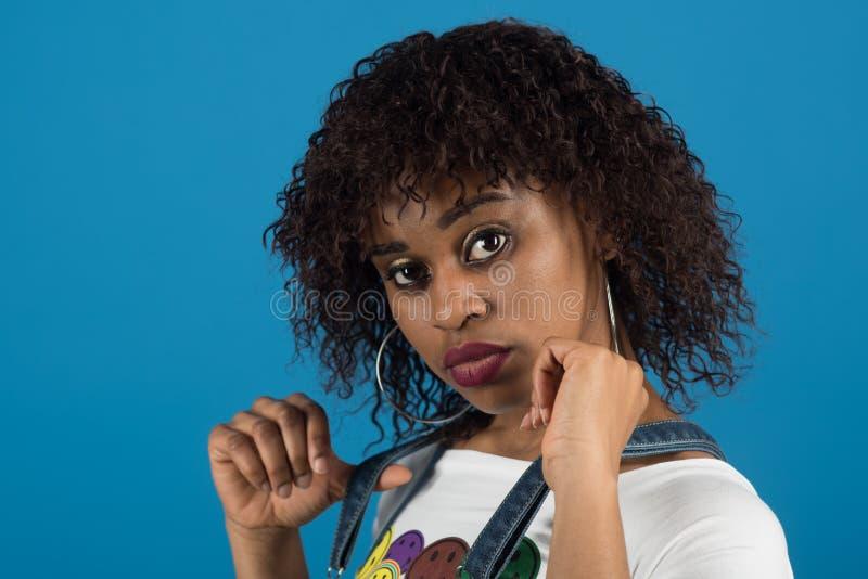 Dam p? lugna framsida med makeup och den afro frisyren Damen med sinnliga kanter rymmer remmar av grov bomullstvilloveraller Kvin arkivbild