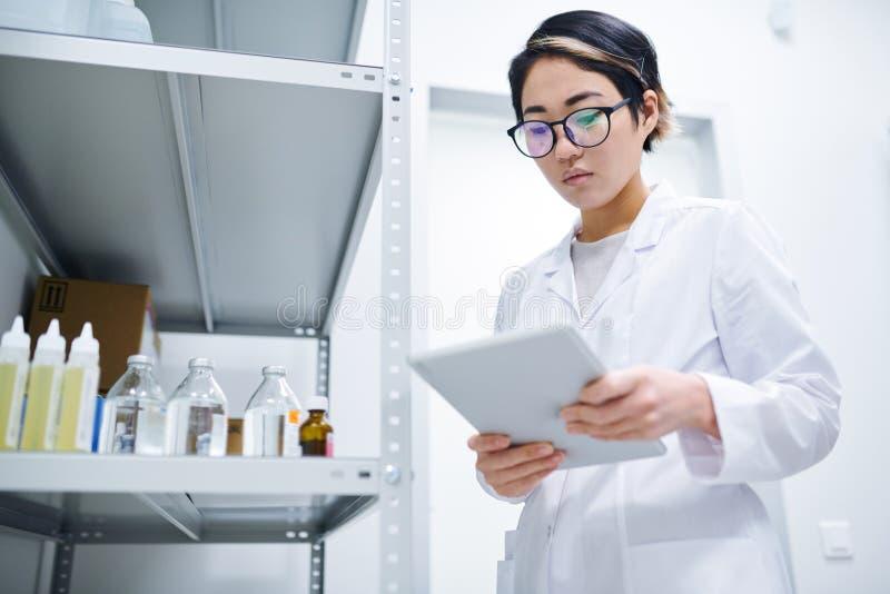 Dam som arbetar i medicinskt lagringsrum royaltyfri fotografi