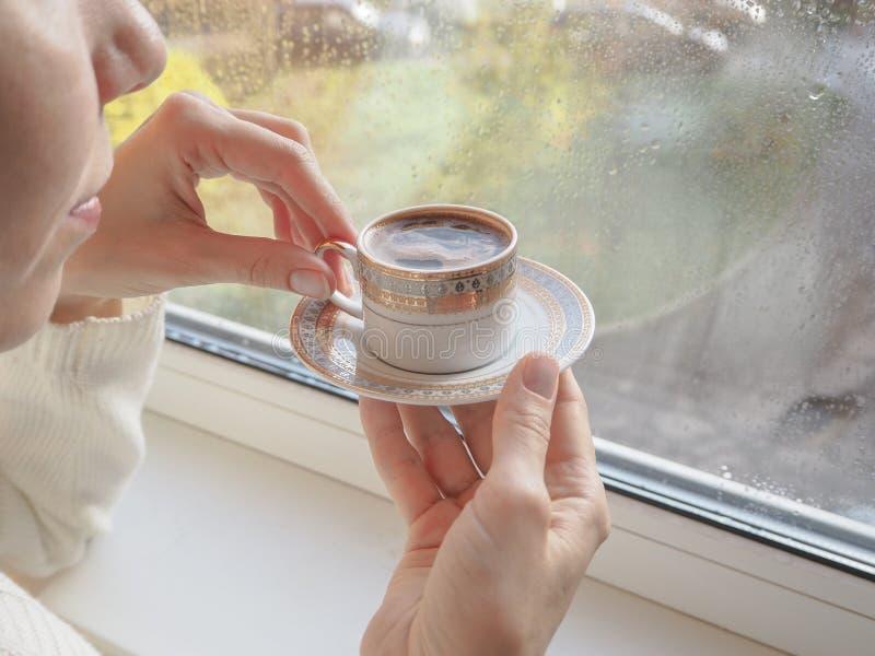 Dam som dricker kaffe vid fönstret royaltyfria bilder