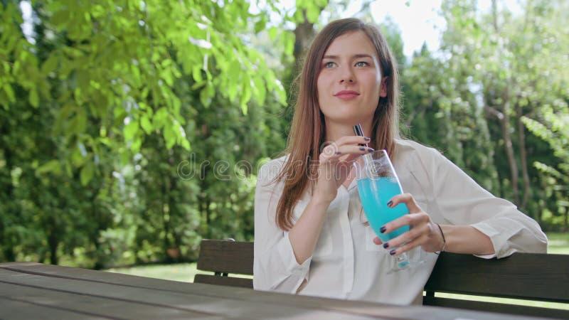 Dam som dricker smoothien i parkera royaltyfria foton