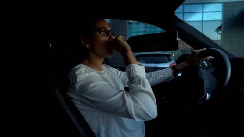 Dam som dricker vin och kör bilen som avlöser spänning, hemfallen person för alkohol arkivbild
