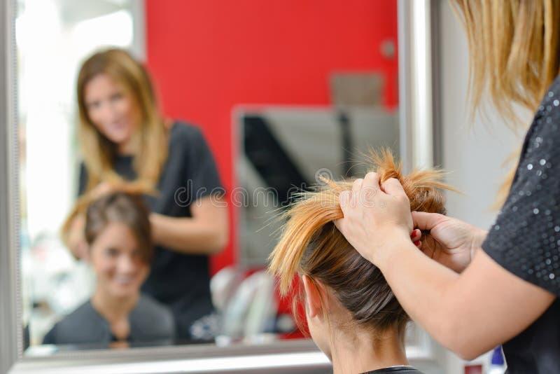 Dam som har hår som sätts upp i frisörer arkivfoto