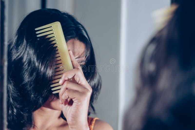 Dam som kammar hennes hår som ser hennes bild på spegeln arkivbild