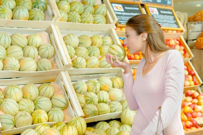 Dam som luktar melon i specerihandlare arkivfoto