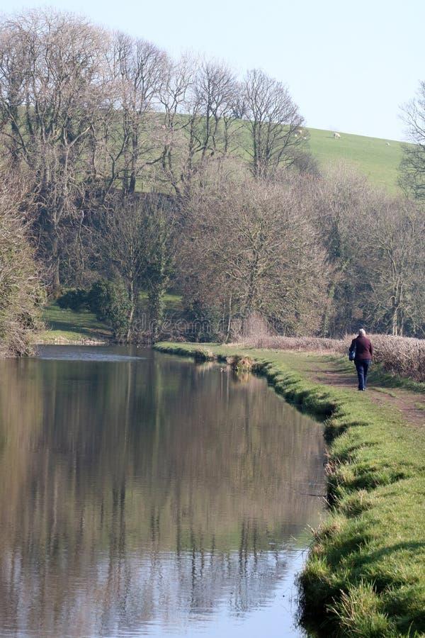 Dam som promenerar kanaldragvägen i bygd royaltyfri bild