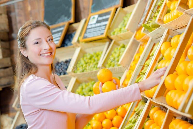 Dam som rymmer apelsiner i grönsakshandlare arkivbild