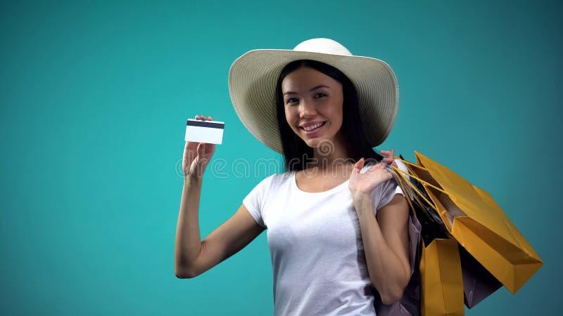 Dam som rymmer shoppingp?sar som visar kreditkorten in i kameran, cashless betalningar arkivbild