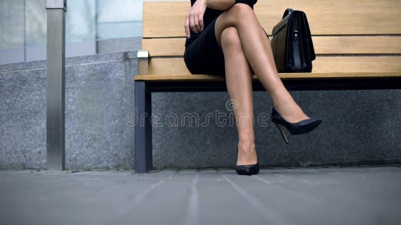 Dam som sitter på bänk, väntande på klient som är trött av att bära hög-heeled skor arkivbilder