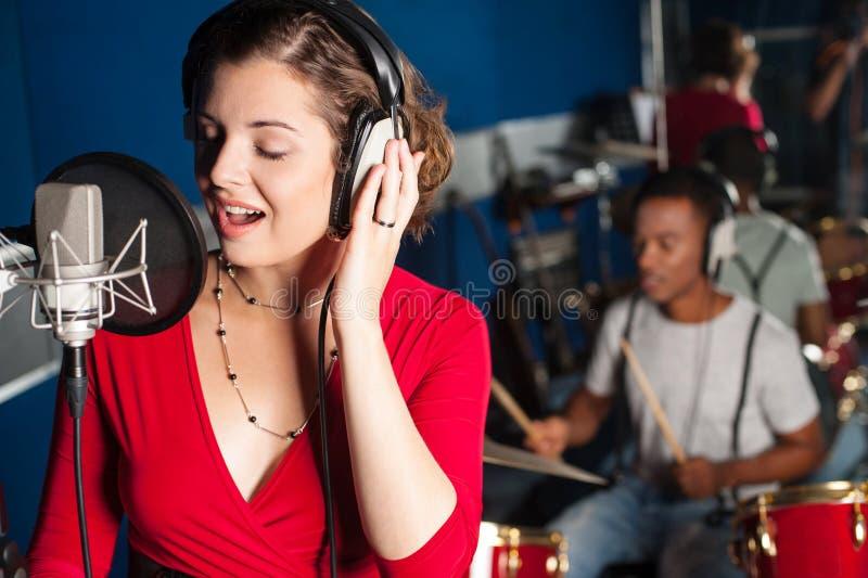Dam som sjunger i inspelningstudio royaltyfri foto