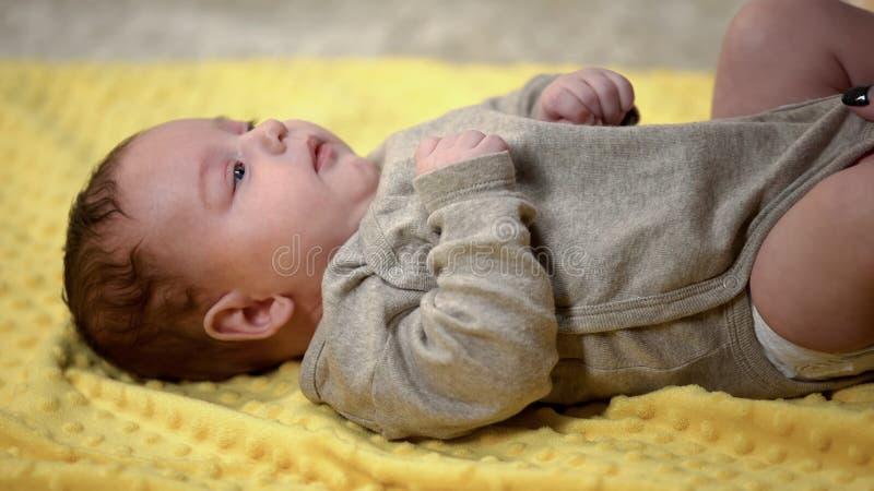 Dam som upp kl?r den gulliga mycket lilla ungen, n?r att ha ?ndrat bl?jor, naturliga kl?der f?r barn royaltyfria bilder