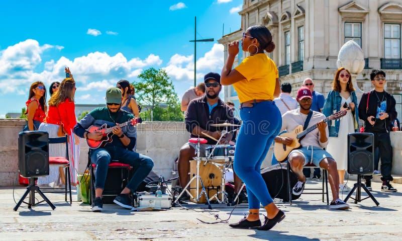 Dama śpiew w Prace De Comercio z jej współczłonkami drużynymi zabawia wszystkie turystycznego odwiedza tejo brzeg rzekiego zdjęcia stock
