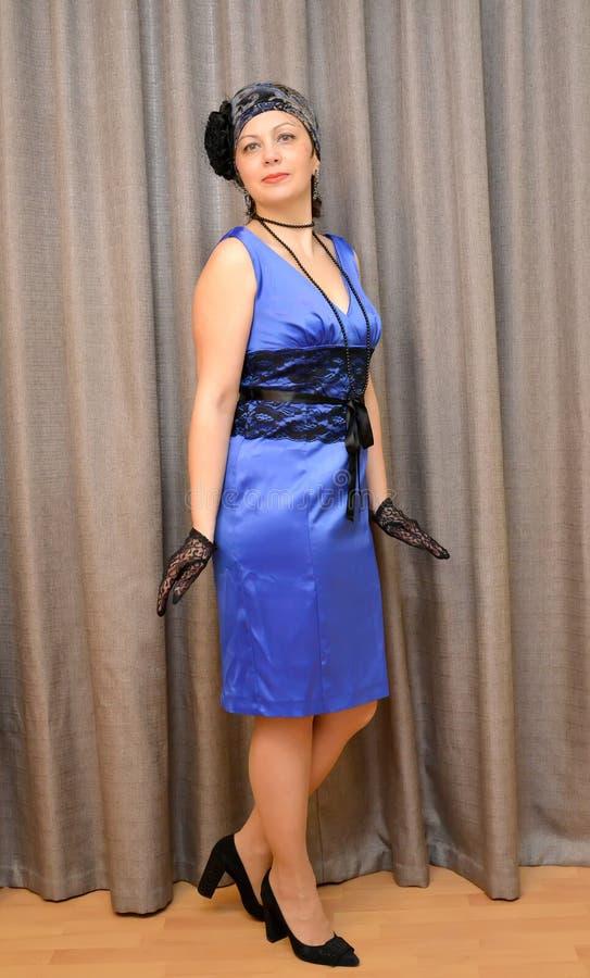 Dama średni rok w błękitnej atłas sukni jest okno zdjęcie stock