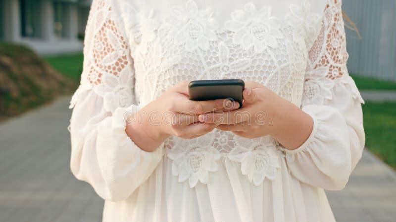 Dama Chodzi telefon i Używa w miasteczku obraz stock