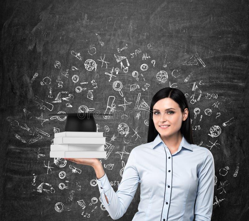 Dama chwytów książki z skalowanie kapeluszem Edukacyjne ikony rysują nad czarną kredową deską zdjęcie royalty free