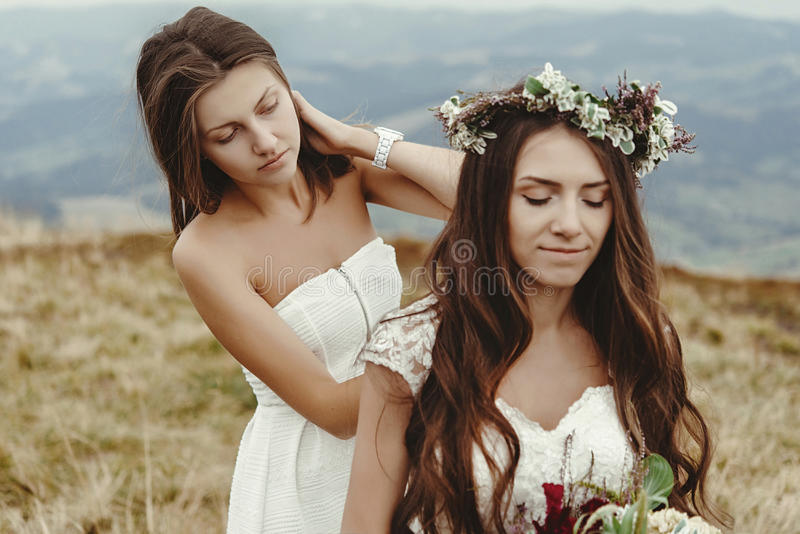 Dama de honor elegante que ayuda a la novia magnífica que se prepara, weddin del boho foto de archivo