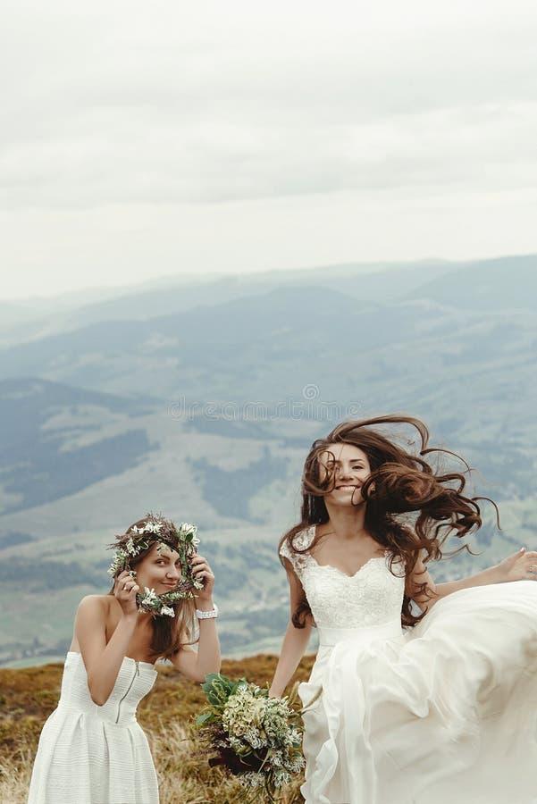 Dama de honor elegante y novia magnífica que se divierten y que saltan, BO imagen de archivo