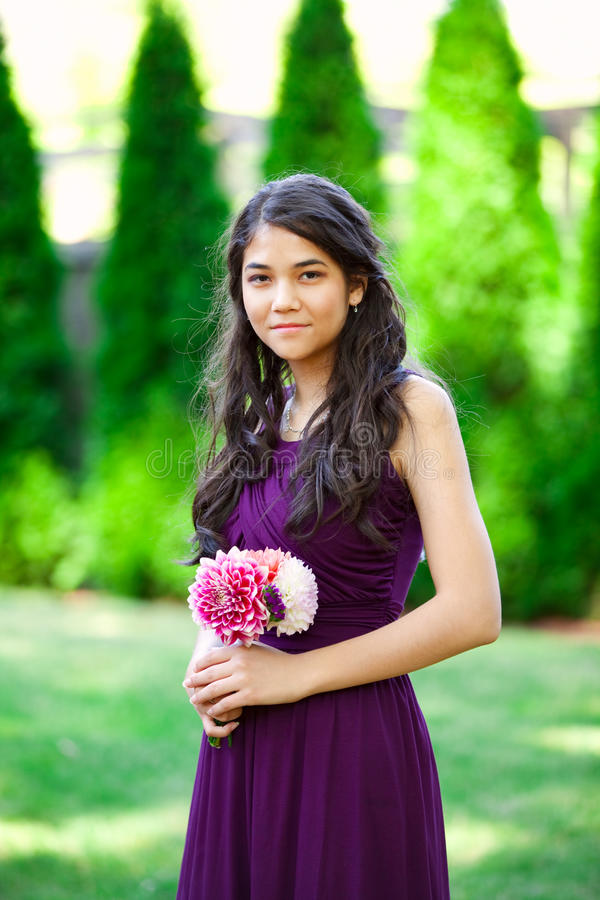 Dama de honra biracial bonita no vestido roxo, sorrindo fotografia de stock royalty free