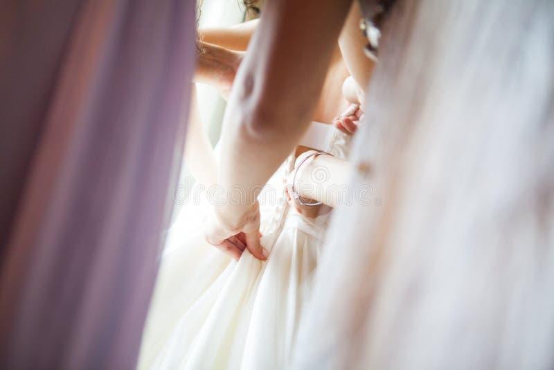 A dama de honra est? ajudando a noiva a vestir-se fotografia de stock royalty free