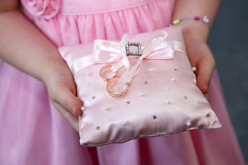 A dama de honra guarda um coxim decorativo com anéis de ouro do casamento foto de stock