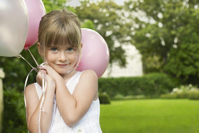 Dama de honra pequena que guarda balões imagem de stock