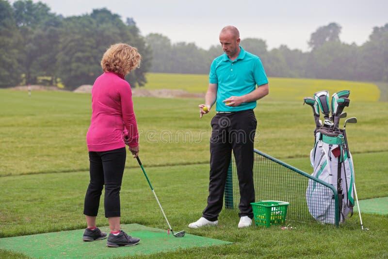 Dama golfista uczy golfowy pro. zdjęcie royalty free