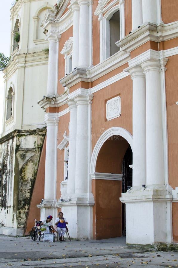 Dama, Niewidomy mężczyzna obok niepełnosprawnego żebraka w wózku inwalidzkim przy Kościelnym jard bramy portalem zdjęcie royalty free
