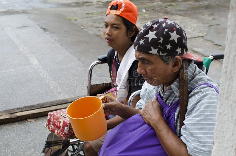 Dama, Niewidomy mężczyzna obok niepełnosprawnego żebraka w wózku inwalidzkim przy Kościelnym jard bramy portalem fotografia stock