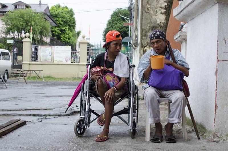 Dama, Niewidomy mężczyzna obok niepełnosprawnego żebraka w wózku inwalidzkim przy Kościelnym jard bramy portalem obraz stock