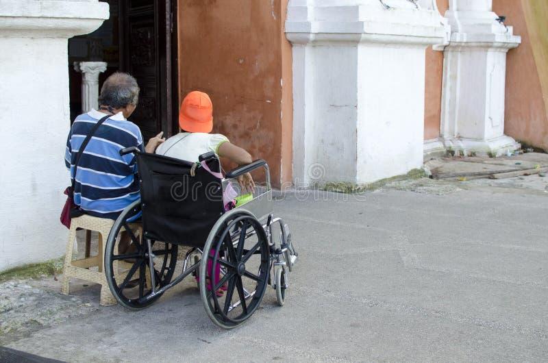 Dama, Niewidomy mężczyzna obok niepełnosprawnego żebraka w wózku inwalidzkim przy Kościelnym jard bramy portalem zdjęcia stock