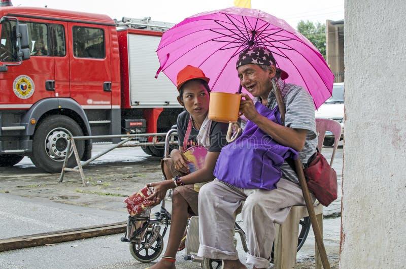 Dama, Niewidomy mężczyzna obok niepełnosprawnego żebraka w wózku inwalidzkim przy Kościelnym jard bramy portalem z parasolem zdjęcie royalty free