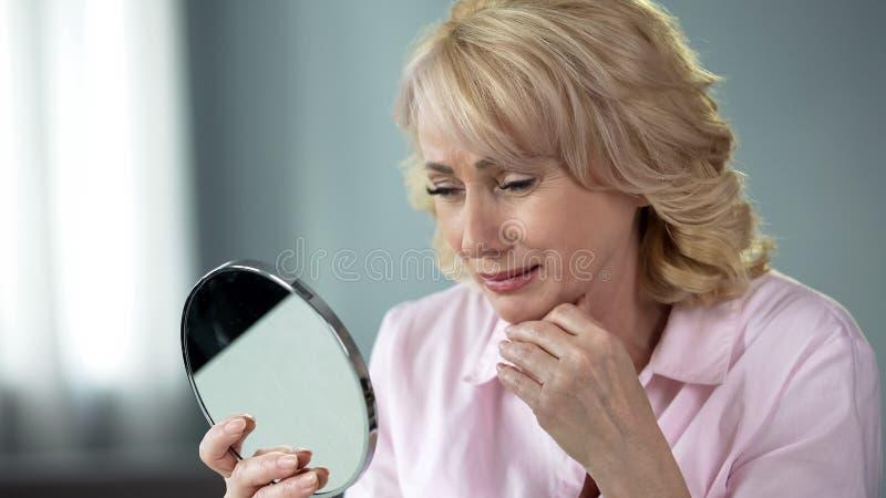 Dama patrzeje w lustrze pamięta młodą i zdrową skórę w jej 50, nostalgia obraz stock