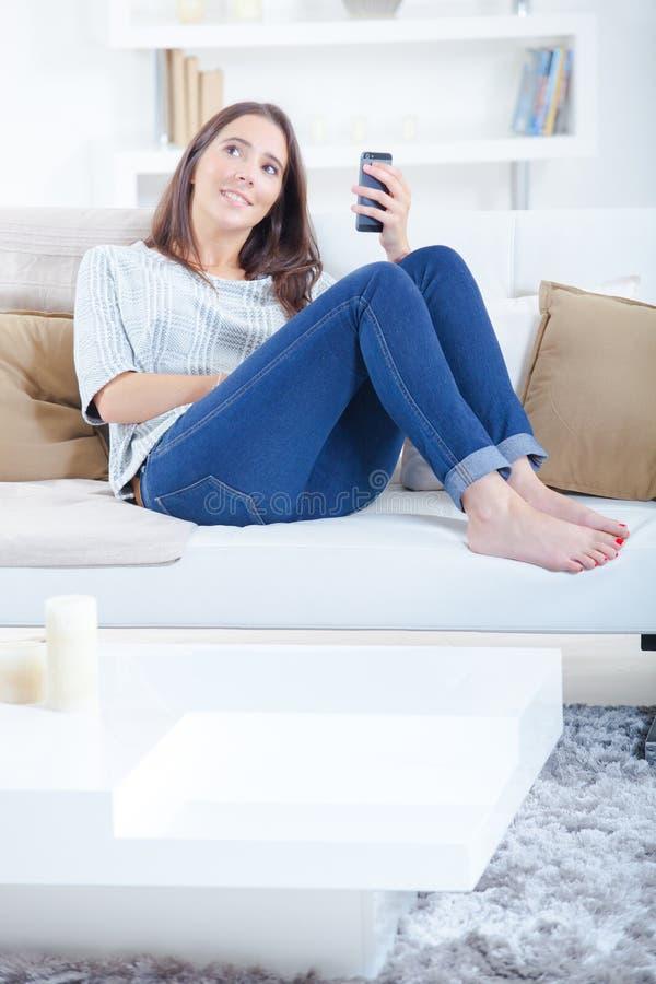 Dama patrzeje w odległość siedział na kanapy mienia telefonie komórkowym obraz royalty free