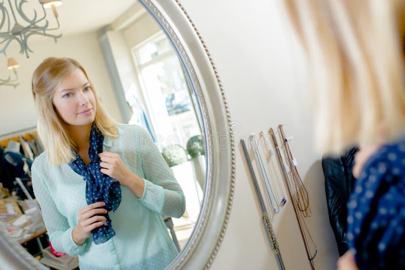 Dama próbuje na szaliku patrzeje odbicie w lustrze zdjęcia stock