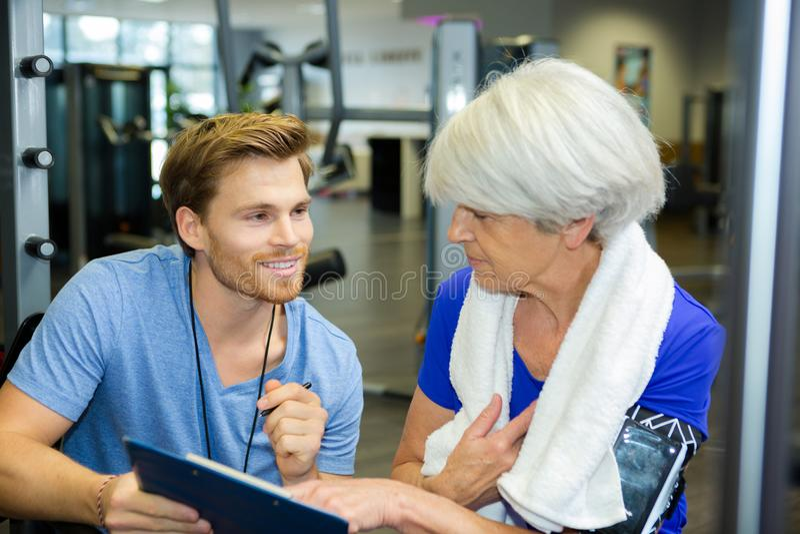 Dama pracująca z życzliwym uśmiechniętym młodym męskim trenerem out obrazy stock