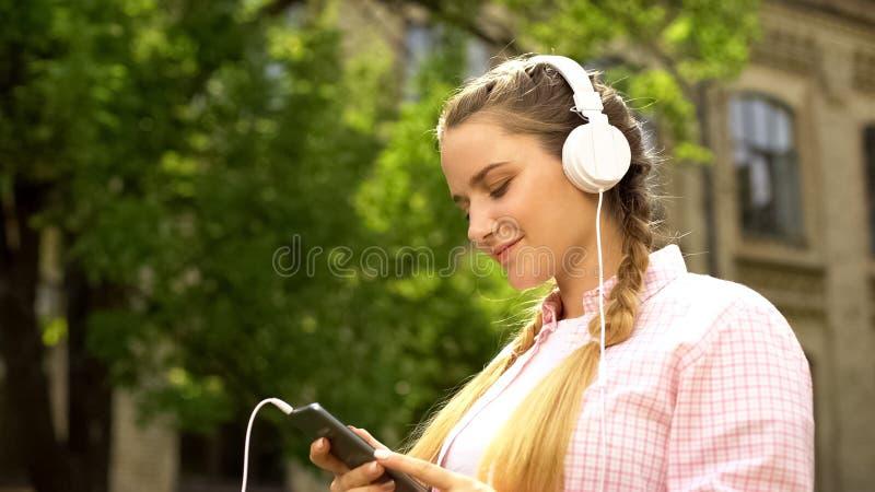 Dama słucha muzyka na wiszącej ozdobie w hełmofonach, app ściąganie, technologie obrazy stock