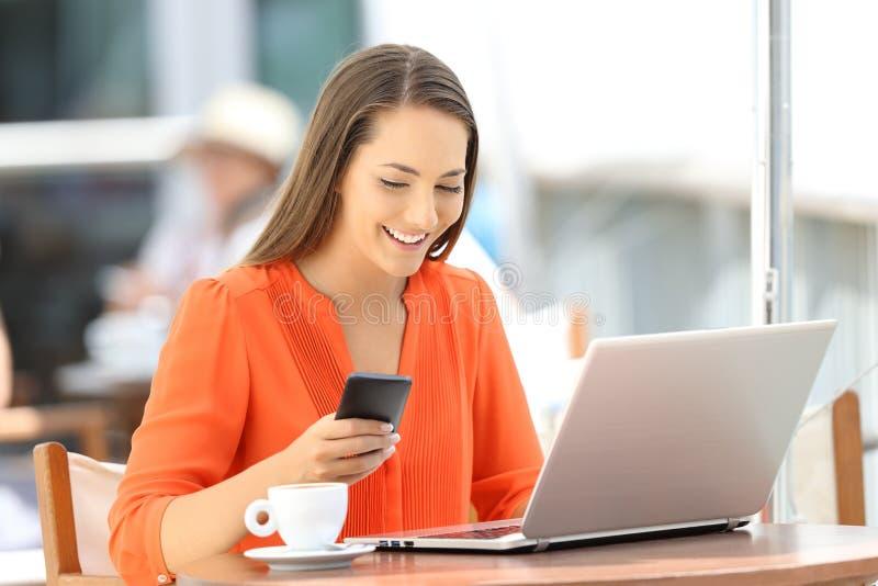 Dama używa laptop i telefon w barze fotografia stock