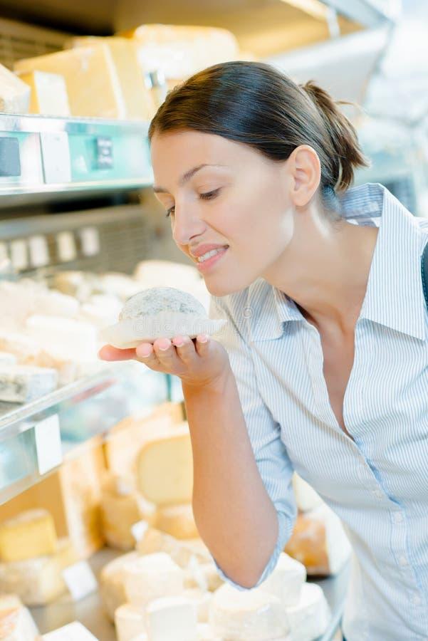 Dama wącha ser w sklepie obrazy stock