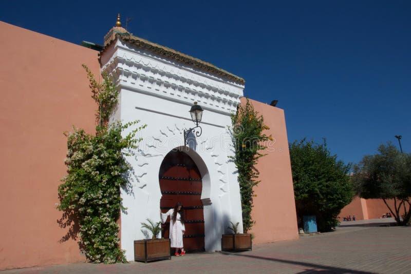 Dama w biały pozować w Marokańskim drzwi zdjęcia royalty free