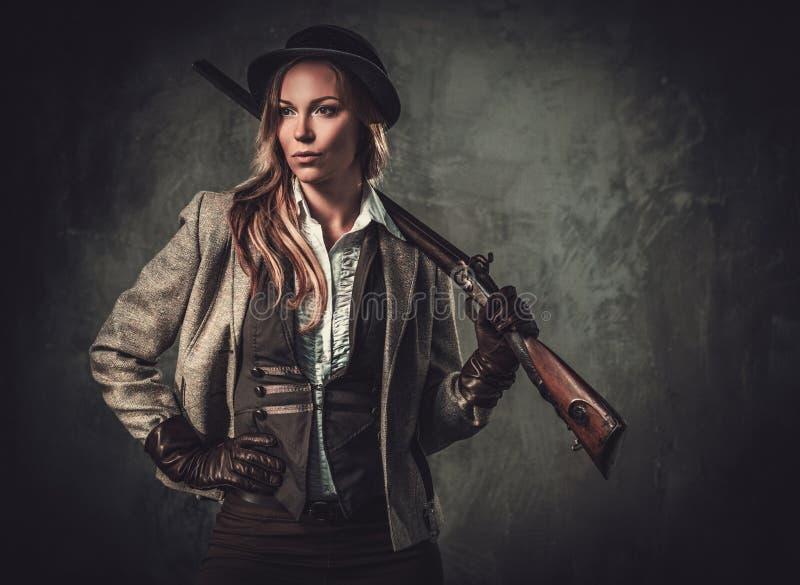 Dama z flintą i kapeluszem od dzikiego zachodu na ciemnym tle fotografia stock