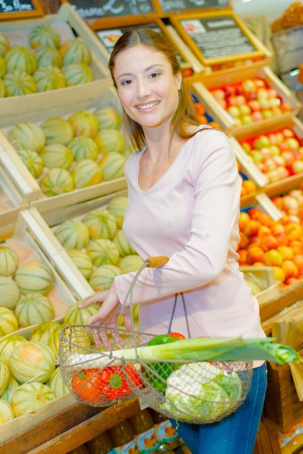 Dama zakupy pozycja obok melonów zdjęcia stock