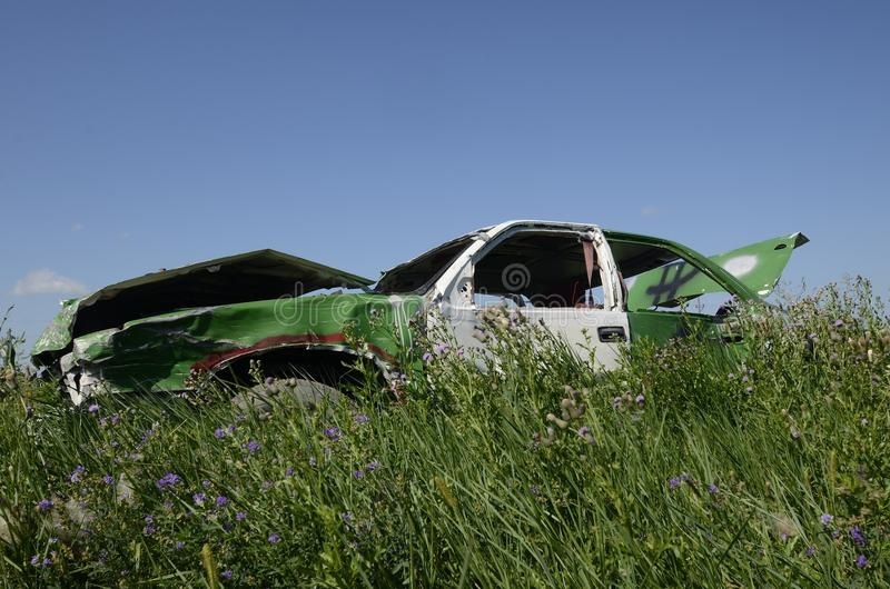 Damage body of a race car. Parked in the weeds and long grass, a car used in races displays extensive damage to the body royalty free stock photos
