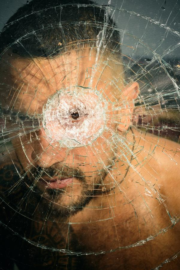 Damage. sexy hispanic man broken mirror. anger. destruction. crush test. theft. emotional discharge. bullet hole in royalty free stock photo