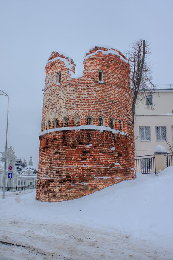 Damaged ancient tower in modern city royalty free stock photography