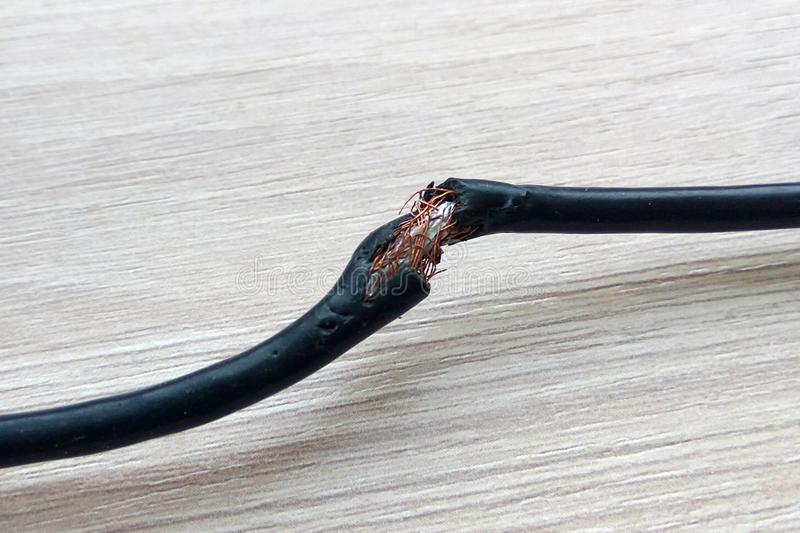 Damaged black electric cord on wooden table or floor background. Dangerous broken electrical cable stock images